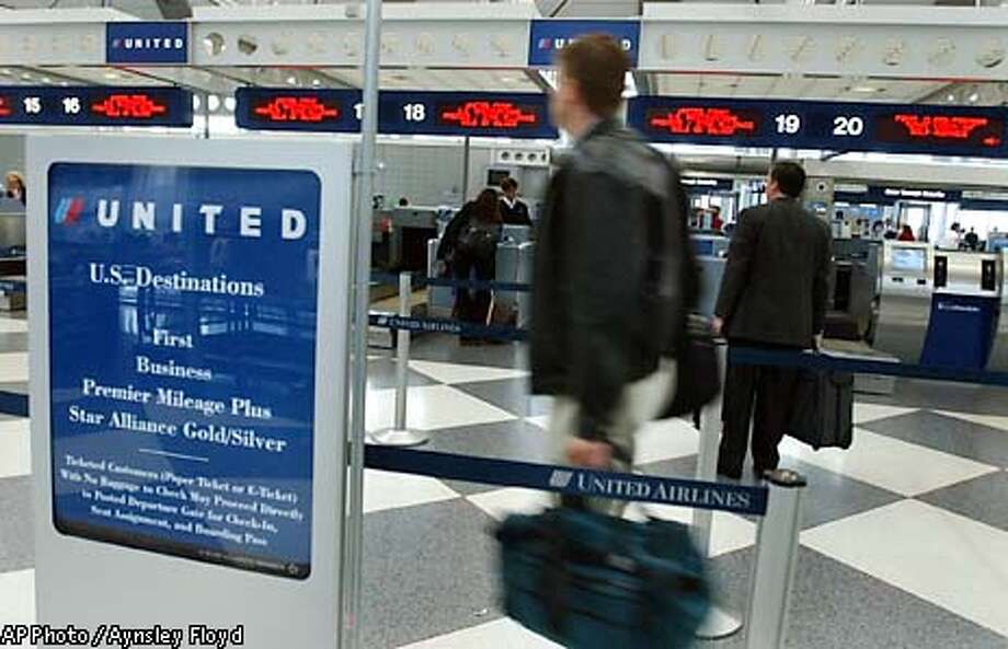 Customers of United Airlines join the ticket line at O'Hare International Airport in Chicago. The parent company of United Airlines reported a $889 million third-quarter loss , Friday, Oct. 18, 2002. (AP Photo/Aynsley Floyd) Photo: AYNSLEY FLOYD