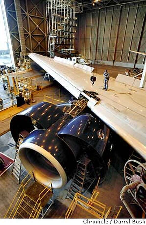 A sheet metal worker stands on the wing of a United Boeing 777 inside a hanger at United Airlines maintenance facility near San Francisco Airport.  Event on 3/3/04 in Millbrae.  Darryl Bush / The Chronicle Photo: Darryl Bush