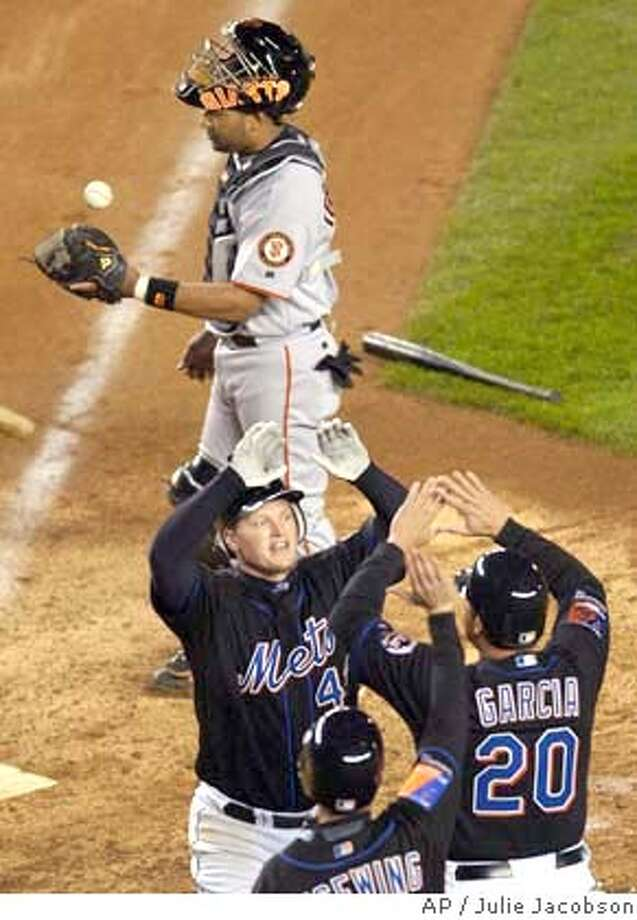 New York Mets' Shane Spencer, center, is greeted by teammates Karim Garcia and Joe McEwing as San Francisco Giants catcher Yorvit Torrealba flips the ball in the air after Spencer hit a three-run home run to break a two-run tie in the eighth inning at Shea Stadium in New York, Wednesday, May 5, 2004. (AP Photo/Julie Jacobson) Photo: JULIE JACOBSON