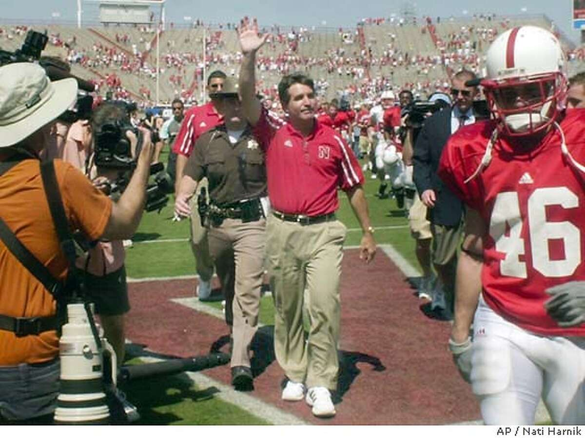 Nebraska coach Bill Callahan, center, waves to the crowd at the end of the annual Red/White spring game in Lincoln, Neb., Saturday, April 17, 2004. It didn't take long for the spring game-record crowd of 61,417 to see Callahan was serious when he promised to overhaul Nebraska's offense. (AP Photo/Nati Harnik)