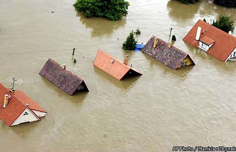 An aerial view of houses at Kralupy, near Prague, which are submerged up to their roofs in flood waters on Wednesday, Aug.14, 2002. (AP Photo/CTK, Stanislav Zbynek) Photo: STANISLAV ZBYNEK