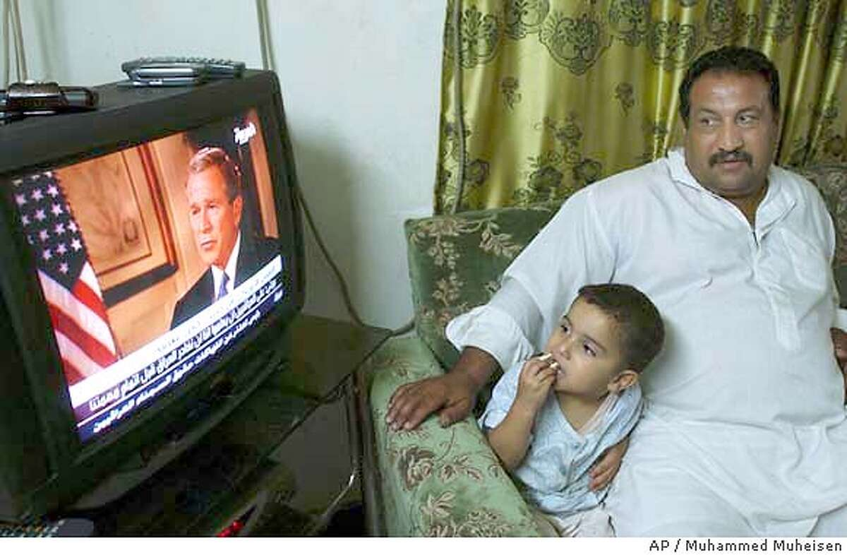 An Iraqi family watches President Bush's interview broadcast on Arab television station Al Arabiya at their home in Baghdad, Iraq, Wednesday, May 5, 2004. Bush said in the interview that the treatment of prisoners at Abu Ghraib prison was