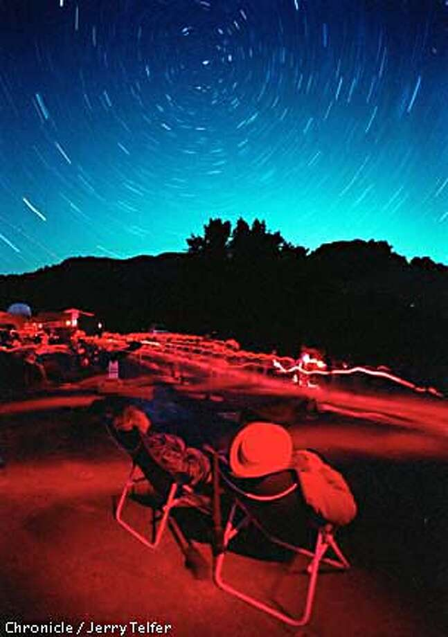 Dickson Yeager and wife B. J. Yeager (cq, right) of Santa Rosa joined hundreds of skywatchers watching the annual Perseid meteor shower at Robert Ferguson Observatory (extreme left) in Sugarloaf Ridge State Park above Kenwood, CA. (Circular streaks in sky are star trails centered on Polaris, caused by long exposure. Streaks on ground are caused by folks with their red-filtered flashlights.)  CHRONICLE STAFF PHOTO BY JERRY TELFER Photo: JERRY TELFER