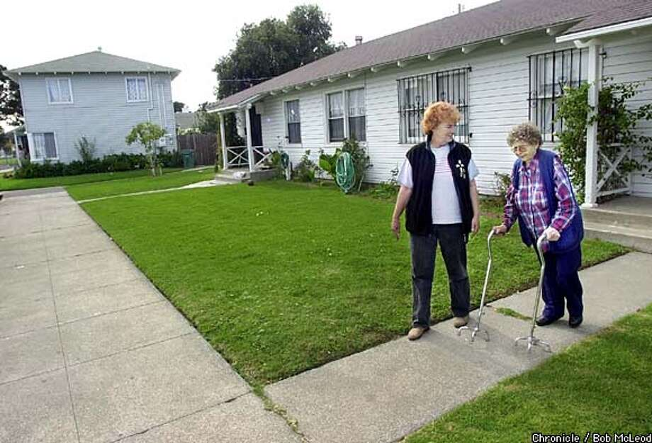 Orien Fitch and Karen Skowronek head out for a stroll in Richmond's Atchison Village. At 80, Fitch is one of the few remaining charter members of the co-op. Little has changed here, prompting villagers to apply to the National Register of Historic Places. Results are pending. Chronicle photo by Bob McLeod