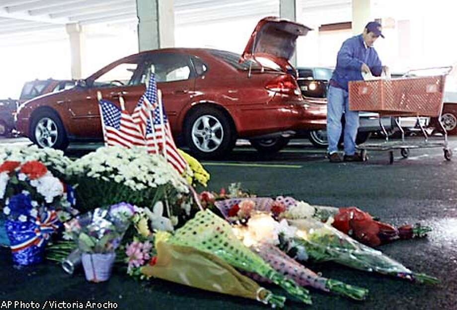 "Freddy Porto of Arlington, Va., removes packages from a Home Depot shopping cart as he loads his trunk just in front of a tribute to the ninth victim of the Washington-area sniper, at the site where Linda Franklin was gunned down, in the parking structre of a Falls Church, Va. Home Depot Wednesday, Oct. 16, 2002. Porto who was parked two spaces away from where the fatal shooting took place was buying fiberglass for his home. ""There are a couple of people who believe they saw a man shoot, unfortunately distance and darkness and perhaps adrenaline have made them unable to give a clear composite that we can disseminate,"" said Montgomery County Police Capt. Nancy Demme. (AP Photo/Victoria Arocho) Photo: VICTORIA AROCHO"