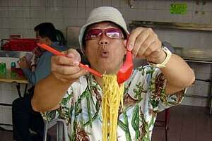 SINGAPORE: KF Seetoh � Singapore hawker food guru KF Seetoh jokingly shows how one should savor a bowl of prawn noodle soup. Photo by Mai Pham/Special to the Chronicle.