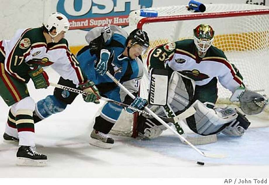 San Jose Sharks' Miroslav Zalesak of the Czech Republic, center, shoots on Minnesota Wild's goalie Manny Fernandez, right, as Filip Kuba of the Czech Republic, left, defends in the first period in San Jose, Calif., Tuesday, March 9, 2004. (AP Photo/John Todd) Photo: JOHN TODD