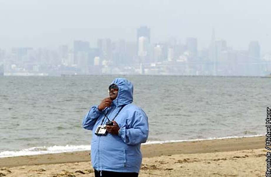 Vernon Reed of Glendale, Arizona tries to keep warm as her strolls along Alameda Beach Tuesday morning. He said when he left Arizona for vacation in the bay Area the temps were in the mid 90's back home. Reed listens to his Ham Radio reciever. by Michael Macor/The Chronicle Photo: MICHAEL MACOR