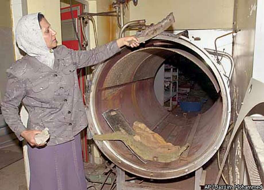 An Iraqi woman shows scraps of a large tube used to produce animal vaccines in a veterinary laboratory in Baghdad Monday Aug. 12, 2002. The lab was closed by the U.N. arms inspectors in 1996. U.N. weapons inspections in Iraq are over, the nation's information minister said Monday in the clearest rejection yet of U.S. and U.N. demands to allow inspectors to return after a four-year standoff. (AP Photo/Jassim Mohammed). Photo: JASSIM MOHAMMED