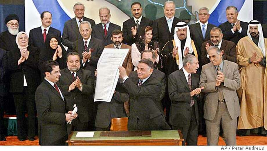 Iraqi Governing Concil member Younadem Kana raises the newly-signed Iraqi interim constitution as other members applaud in the background during signing ceremony Monday March 8, 2004 in Baghdad, Iraq. The signing came after the council members finally resolved a political impasse which was sparked by objections from the country's most powerful cleric. The signing was a key step in U.S. plans to hand over power to the Iraqis. (AP Photo/Peter Andrews) Photo: PETER ANDREWS