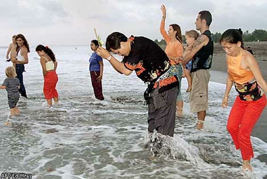 Foreigners and local Balinese offer prayers in the ocean Monday October 14, 2002 in memory of friends who died in Saturday night's bomb explosion at a popular Kuta, Bali night club. Nearly 200 people were killed and hundreds injured when what is believed to be a car bomb exploded in the early hours of Sunday. (AP Photo/Ed Wray) Photo: ED WRAY