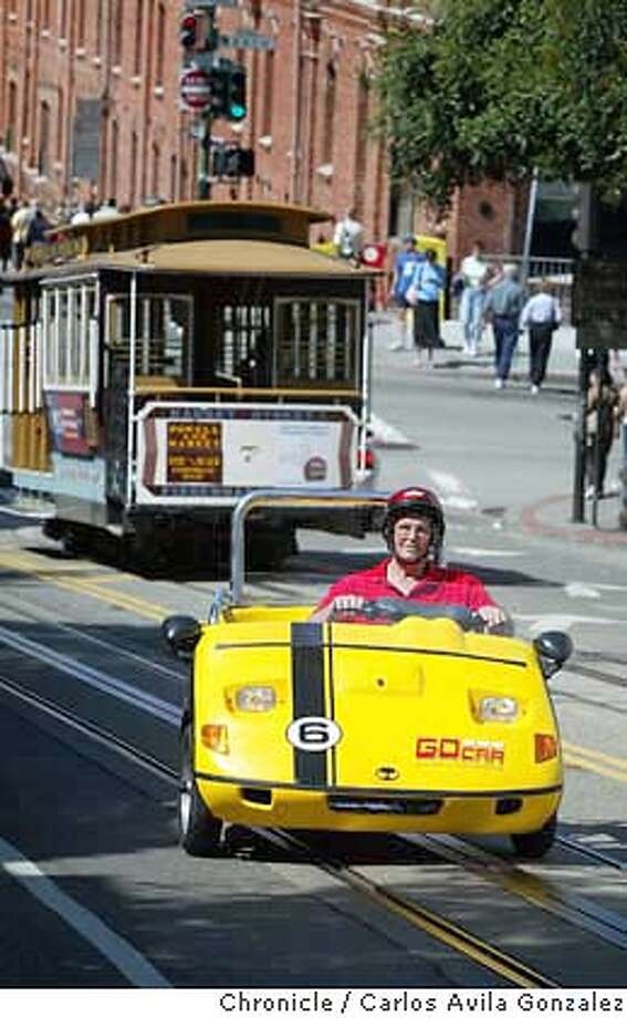 Tom Ruddick of Muncie, Indiana, drives up Hyde Street in a GoCar motorized cart, one of eight that have become big hits with tourists and San Francisco natives alike. The new SF company called GoCar Rentals is renting two-seat moped cars equipped with a Global Positioning System giving tourists an automated talking guided tour of SF. The company uses a Trigger Scooter Car, a bright yellow three-wheeled vehicle that looks like a golf cart  Photo taken on 04/29/04 in San Francisco, Ca. Photo By Carlos Avila Gonzalez / The San Francisco Chronicle Photo: Carlos Avila Gonzalez
