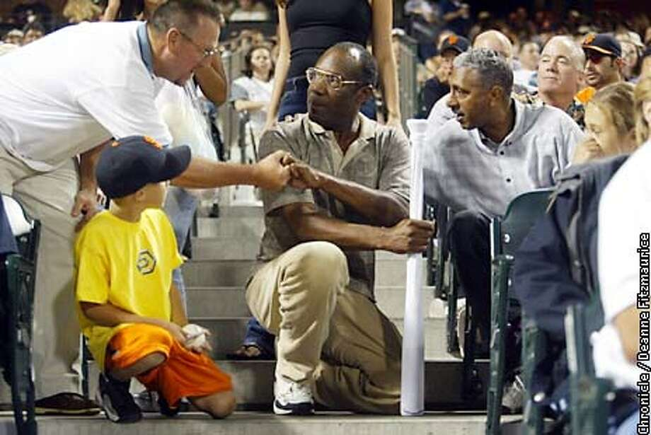 Bobby Bonds, Barry's father, holds the bat that hit No. 600 while shaking hands with a fan. He had cancer surgery a month ago, but vowed last week to see every game until Barry hit No. 600. Chronicle photo by Deanne Fitzmaurice