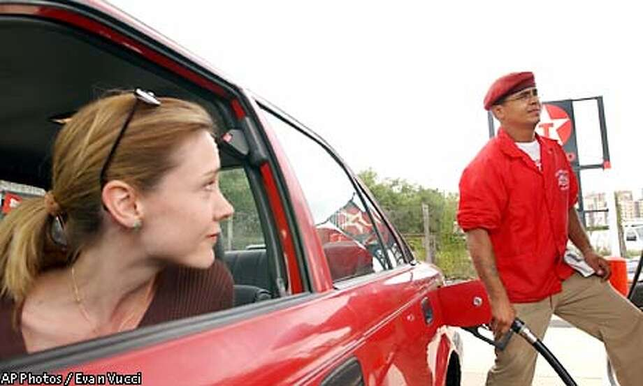 Monique McNamara, of Alexandria Va., looks at Raul Lopez, of the New York chapter of the Guardian Angels, as he pumps gas for her at a gas station in Alexandria, Va., Saturday Oct. 12, 2002, a day after a sniper attacked for the tenth time at a gas station in Fredericksburg, Va. (AP Photos/Evan Vucci) Photo: EVAN VUCCI