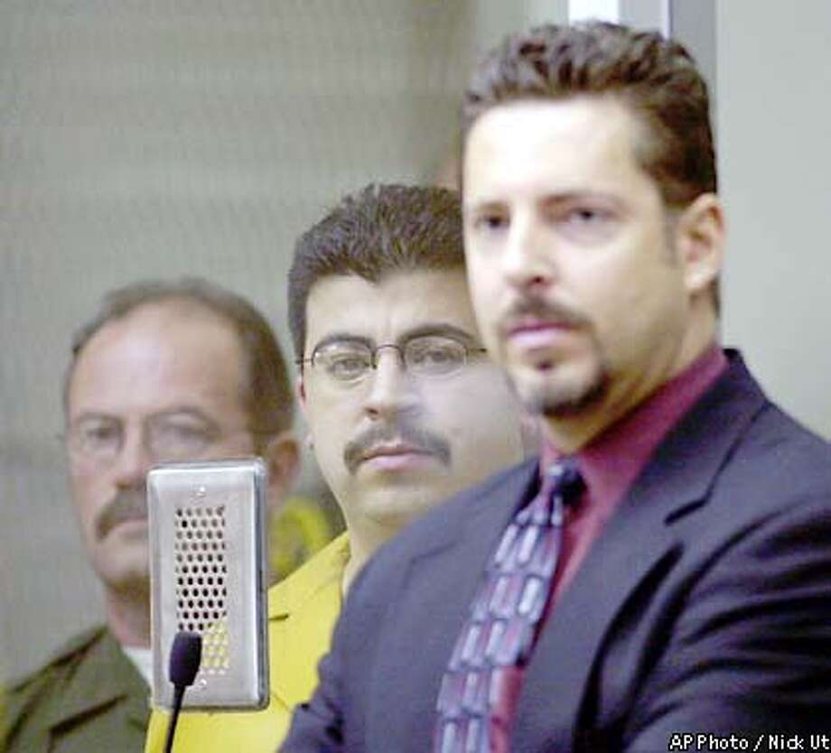 Alejandro Avila, center, accused of kidnapping and killing 5-year-old Samantha Runnion, stands behind bulletproof glass with his public defender Philip L. Zalewski, right. in a courtroom during his arraignment, Friday Aug. 9, 2002, in Santa Ana, Calif. He pleaded innocent as prosecutors investigated additional claims against him in a separate case. (AP Photo/Nick Ut) Photo: NICK UT