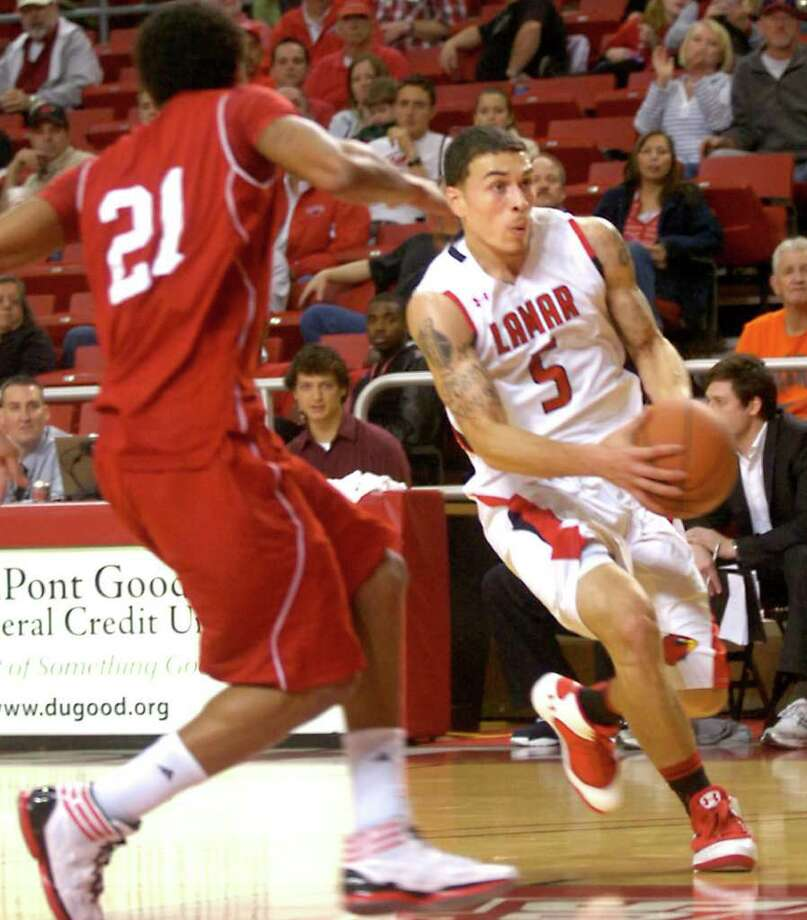 Lamar's Mike James drives to the basket as Nicholls' Shane Rillieux moves in to defend at the Montagne Center in Beaumont, Saturday, January 28, 2012. Tammy McKinley/The Enterprise Photo: TAMMY MCKINLEY