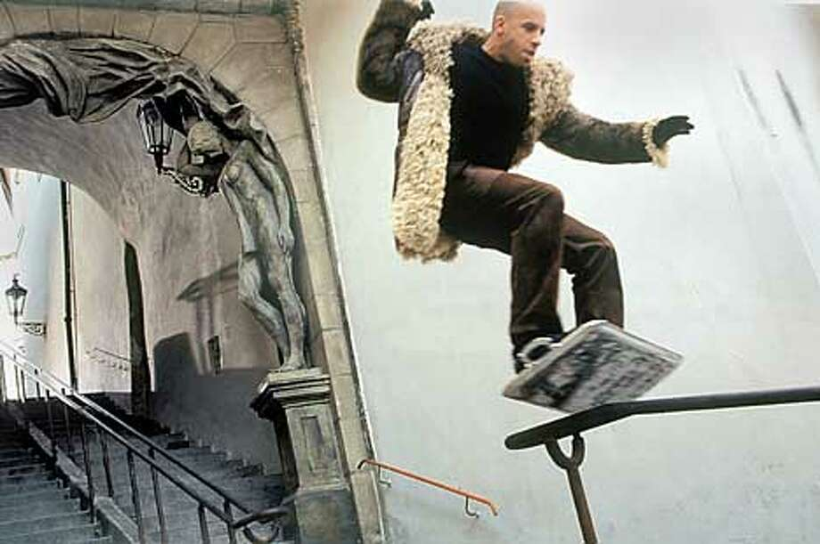 "Vin Diesel skateboards down a bannister on a metal tray as the cynical, poised action hero of ""XXX."""