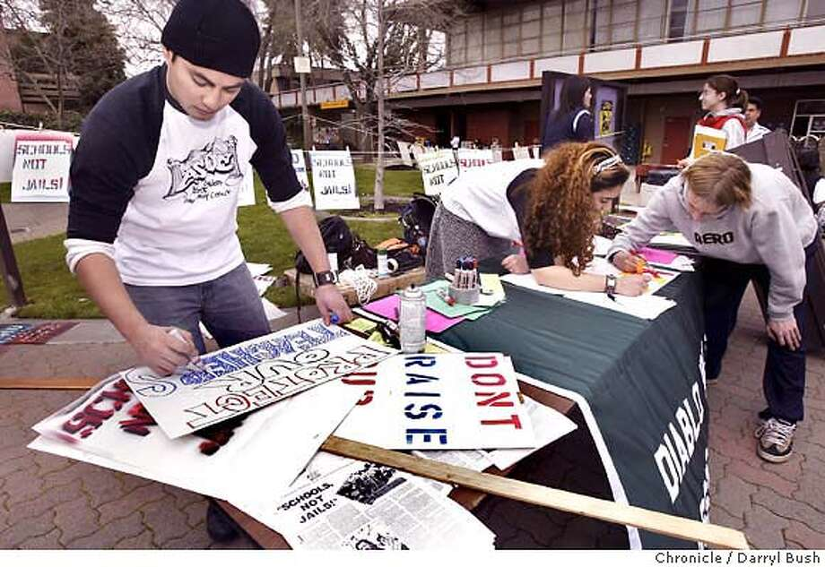 Jeffrey Mandap, 25, student body president, makes a sign along with Carma Hassan (student body secretary) and Clint Woycehoski, 22, of Sacramento (not a student but lending a hand), far right, at back of the table, working on signs in the main quad at Diablo Valley College. Students will use the signs to protest cutbacks to community colleges on Monday at the College Board of Trustees.  Event on 2/5/03 in Pleasant Hill.  Darryl Bush / The Chronicle Photo: Darryl Bush