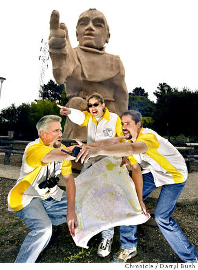 Former Stanford students Brent Holman (left), his wife, Linda, and Martin Reinfried re-enact The Game in front of a statue of Father Junipero Serra off Interstate 280. They and other alumni help run the scavenger hunt. Chronicle photo by Darryl Bush