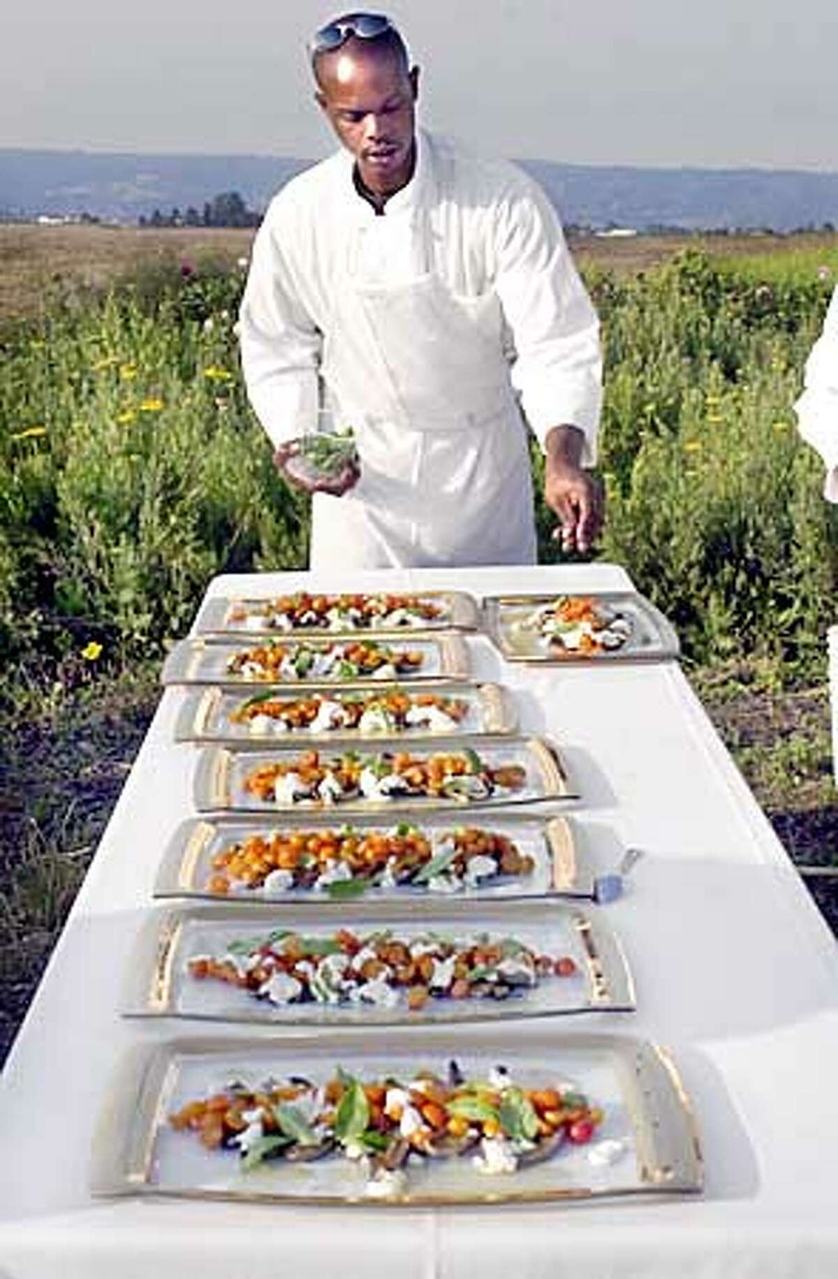 Guest Chef Damani Thomas of Oswald restaurant in Santa Cruz puts the finishing touch on the grilled eggplant with homemade ricotta cheese and cherry tomatoes for the Outstanding in the Field farm dinner and tour at High Ground Farm in Watsonville which featured a six course dinner and farm tour. Photo by Gina Gayle/The SF Chronicle.