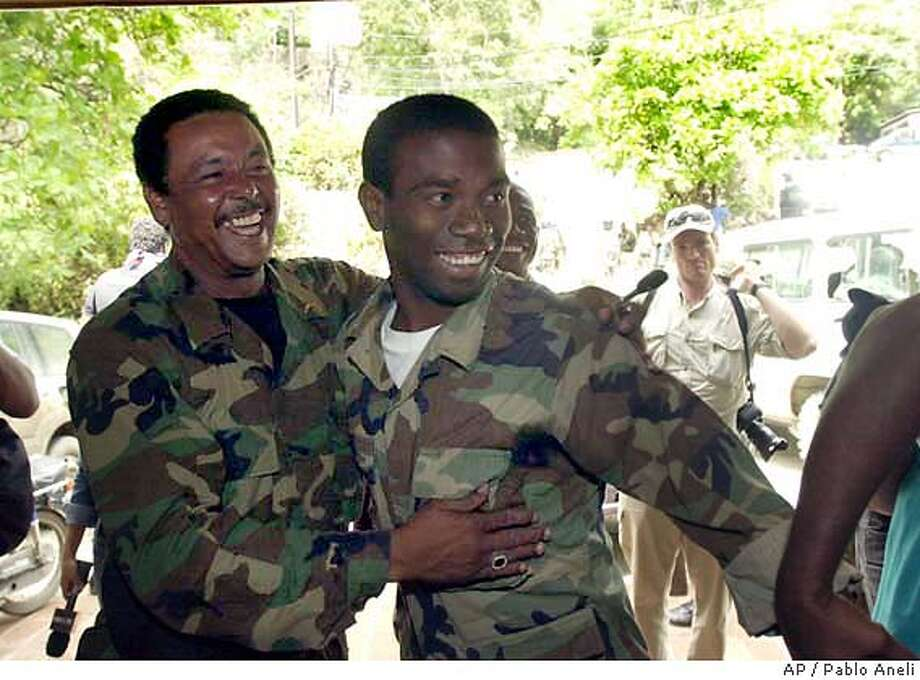 Rebel leaders Louis-Jodel Chamblain, left, and Guy Philippe celebrate after news of President Jean-Bertrand Aristide's departure reached northern Cap-Haitien, Haiti, Sunday, Feb. 29, 2004. (AP Photo/Pablo Aneli). Louis-Jodel Chamblain (left) and Guy Philippe celebrate on the news reaching Cap-Haitien on Sunday of Aristide's departure. Photo: PABLO ANELI