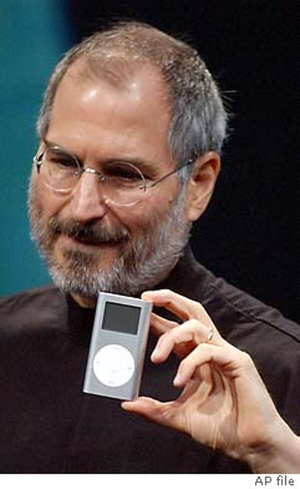 ** FILE ** Apple CEO Steve Jobs displays his company's Mini-Ipod at the Macworld Conference and Expo in San Francisco on Tuesday, Jan 6, 2004. Apple Computer Inc. is investigating complaints that its popular iPod mini is prone to static and other sound distortions when playing back music. (AP Photo/Marcio Jose Sanchez)