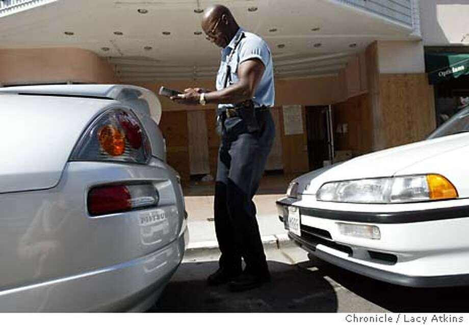 Aaron James, a parking control agent ,issues a parking ticket along Chestnut street.Tuesday April.27 2004, in San Francisco.  LACY ATKINS / The Chronicle Photo: LACY ATKINS