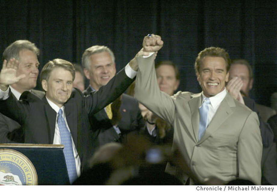 State Controller Steve Westly, left, raises Arnold Schwarzenegger's hand in a victory salute. Chronicle photo by Michael Maloney