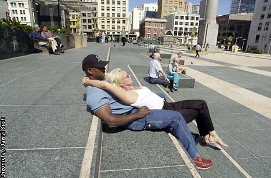 Anthony Nance and Jennifer Sharpe of Alameda enjoy the sunshine as they rest on the concrete slab stairs that are near the main stage area of the new Union Square in San Francisco. Chronicle Photo by Darryl Bush Photo: Darryl Bush