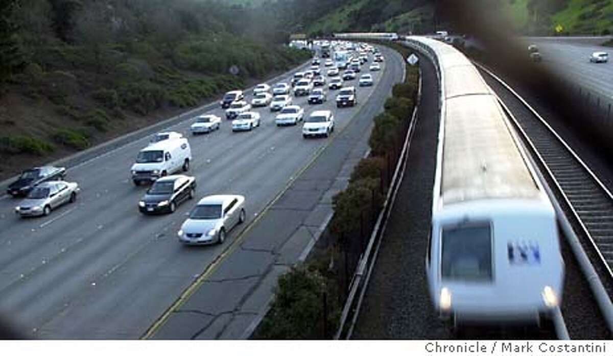 A BART train blows by traffic along Highway 24.