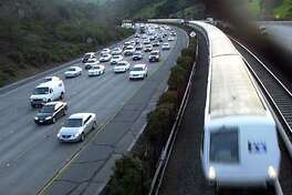 transit03_0145.JPG Photo taken on 3/02/04 in Orinda. A Bart train blows by traffic along 24. For election story on Measure 2. CHRONICLE PHOTO BY MARK COSTANTINI
