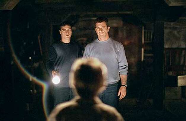 Joaquin Phoenix and Mel Gibson in a scene from SIGNS.  (HANDOUT PHOTO) Photo: HANDOUT