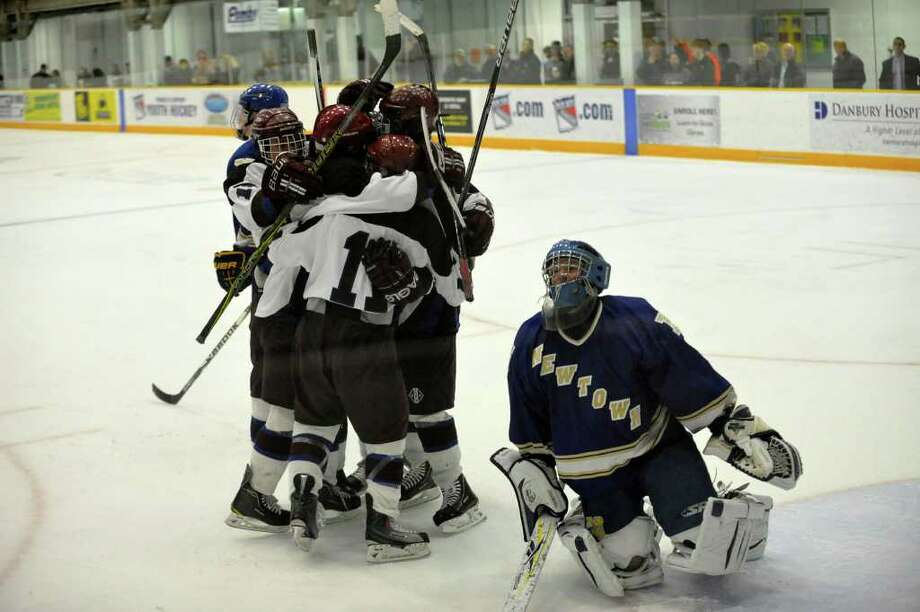 Brookfield/Bethel/Danbury teammates congratulate Stephen Hallock after he scored the winning goal on Newtown goalie Michael Allwein in overtime at the Danbury Ice Arena on Saturday, Jan. 28, 2012. Brookfield/Bethel/Danbury won 4-3. Photo: Jason Rearick / The News-Times