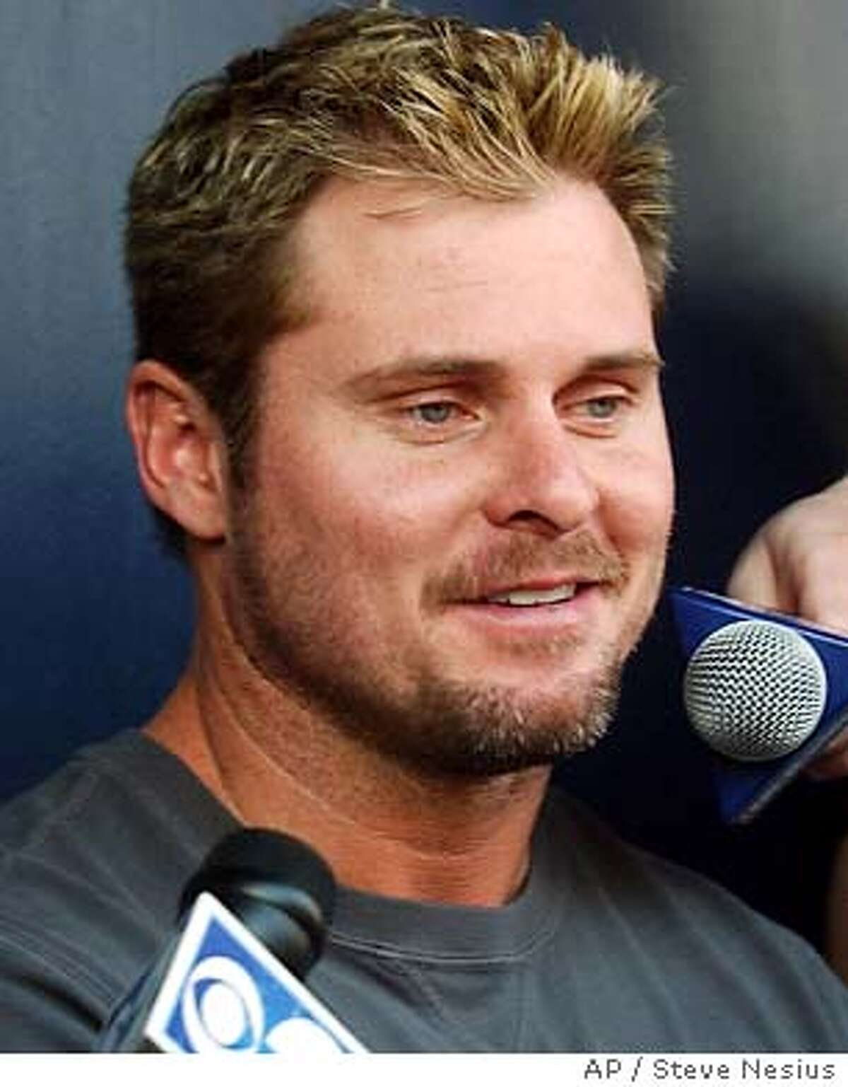 New York Yankees ' Jason Giambi talks with the media in the dugout at spring training camp Monday, Feb. 23, 2004 at Legends Field in Tampa, Fla. Position players report Tuesday for their first team workout. (AP Photo/Steve Nesius)