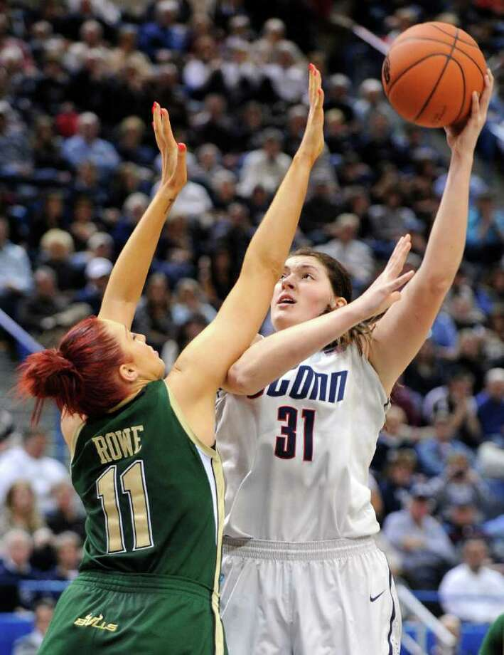 Connecticut's Stephanie Dolson, right, shoots over South Florida's Caitlin Rowe during the second half of an NCAA college basketball game in Hartford, Conn., on Saturday, Jan. 28, 2012. Dolson scored 22 points and had 18 rebounds in Connecticut's 77-62 victory. (AP Photo/Fred Beckham) Photo: Fred Beckham, Associated Press / FR153656 AP