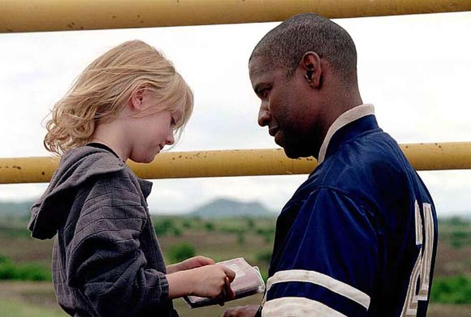 "A Burned-out bodyguard (Denzel Washington) slowly warms up to the daughter of a wealthy family (Dakota Fanning) , whom he has been hired to protect in ""Man on Fire."" (AP Photo/Stephen Vaughan) Photo: STEPHEN VAUGHAN"