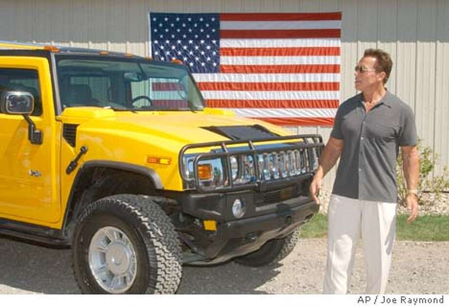 ** FILE ** Arnold Schwarzenegger stands in front of a Hummer H2 in this Aug. 8, 2002, file photo taken in South Bend, Ind. Schwarzenegger announced he planned to retrofit one of his Hummers to run on eco-friendly hydrogen. (AP Photo/Joe Raymond) Photo: JOE RAYMOND