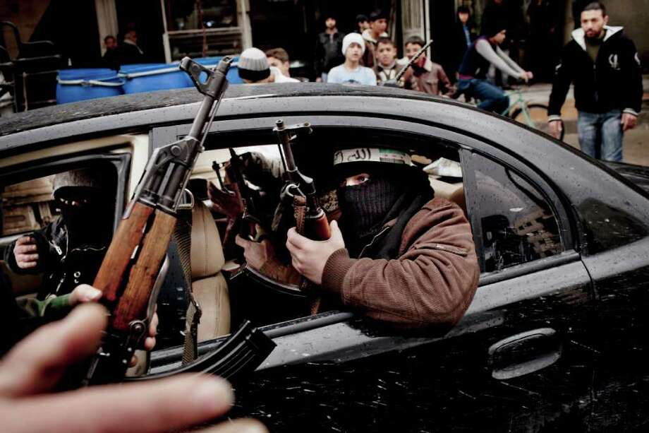 The Free Syrian Army militia patrols the streets of the Damascus suburb of Saqba on Friday. Bloodshed from the government shelling towns and shooting protesters led Arab League monitors to end their mission. Photo: TOMAS MUNITA / NYTNS