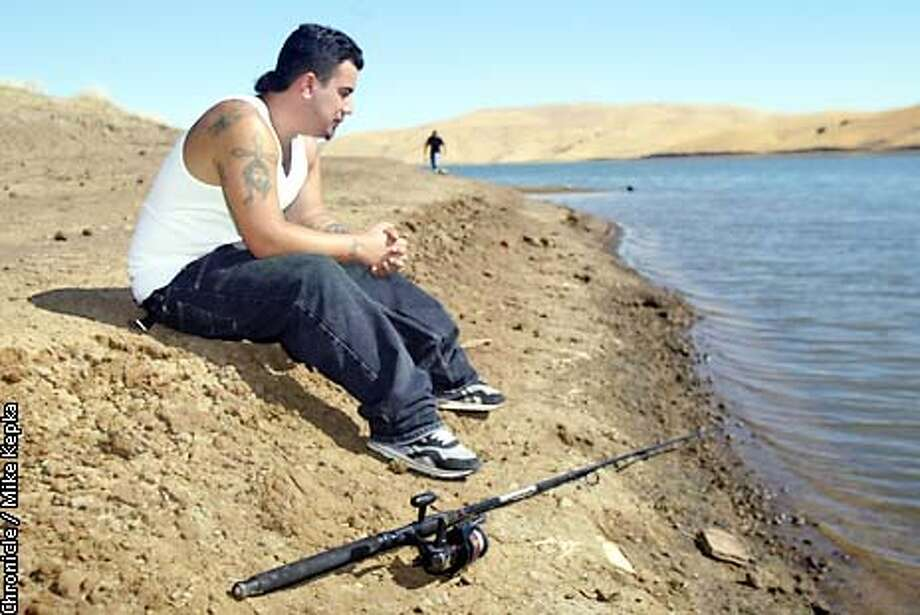 Mark Gallegos of Antioch waits for the trout to take his line at his favorite fishing spot at Los Vaqueros Reservoir. BY MIKE KEPKA/THE CHRONICLE Photo: MIKE KEPKA