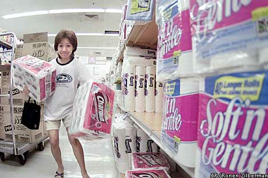 Shopper Reiko Chinei stocks up on toilet paper at Star Market, Tuesday, Oct. 1, 2002, in Honolulu. A drawn out work stoppage at ports on the West Coast could result in a shortage of consumer goods in Hawaii. Hawaii Gov. Cayetano has asked the Pacific Marine Association and the dockworkers union for an exemption that would allow goods and supplies to be shipped to Hawaii. Cayetano says a prolonged labor dispute will have a devastating effect on the economy and morale of Hawaii. (AP Photo/Ronen Zilberman) Photo: RONEN ZILBERMAN