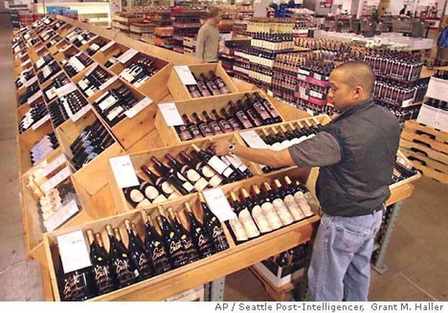 Fred Borja stocks wine at a Seattle Costco store. Costco filed suit against Washington state over alcohol sales and distribution laws. Seattle Post-Intelligencer photo by Grant M. Haller via Associated Press