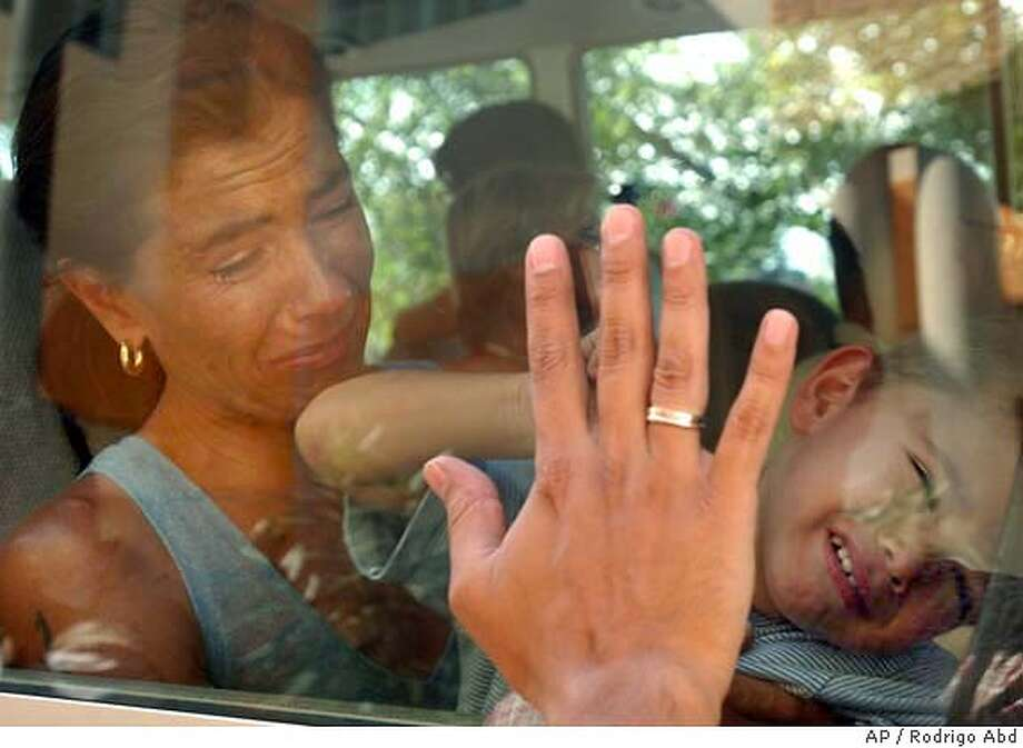 Pablo Isla places his hand on the window of a bus to bid farewell to his wife Ana and son leaving on a bus from the a UN compound in Port-au-Prince, Haiti Thursday, Feb. 26, 2004. Pablo, a Peruvian-Belgian United Nations officer stayed in Haiti, but sent his family away. (AP Photo/Rodrigo Abd) Photo: RODRIGO ABD
