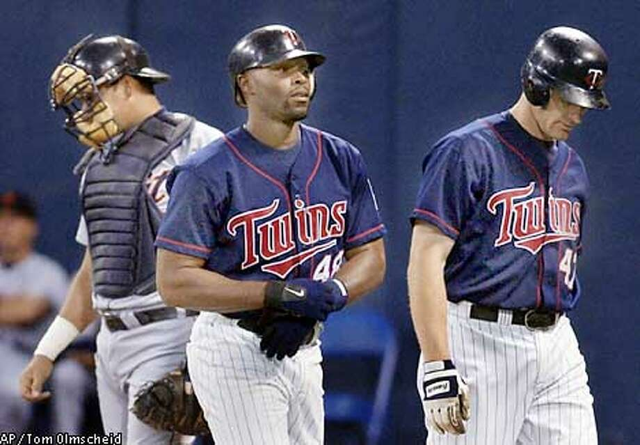 Minnesota Twins' Torii Hunter, center, and Corey Koskie, right, head back to the dugout after Hunter's three-run homerun in the first inning as Detroit Tigers catcher Mike Rivera, left, waits for the next batter Tuesday, Sept. 10, 2002, in Minneapolis. The Twins' Cristian Guzman also scored on the play. The Twins won, 11-4.(AP Photo/Tom Olmscheid) Photo: TOM OLMSCHEID