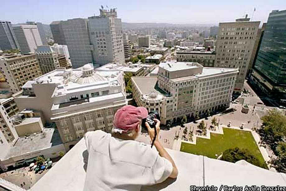 "Bill Caldwell is blasting through time, preparing a lavish gift for Oakland's 150th birthday this summer: a """"rephotoraphy'' project, which he work on here, photographing the Oakland City Center on Monday, July 1, 2002, from the roof of the Oakland City Hall. In the 104-page book, Caldwell rephotographs historic photos from the same spot and the same angle. A corresponding Web site allows users to click on historic pictures and watch the image convert to modern day. (BY CARLOS AVILA GONZALEZ/THE SAN FRANCISCO CHRONICLE) Photo: CARLOS AVILA GONZALEZ"