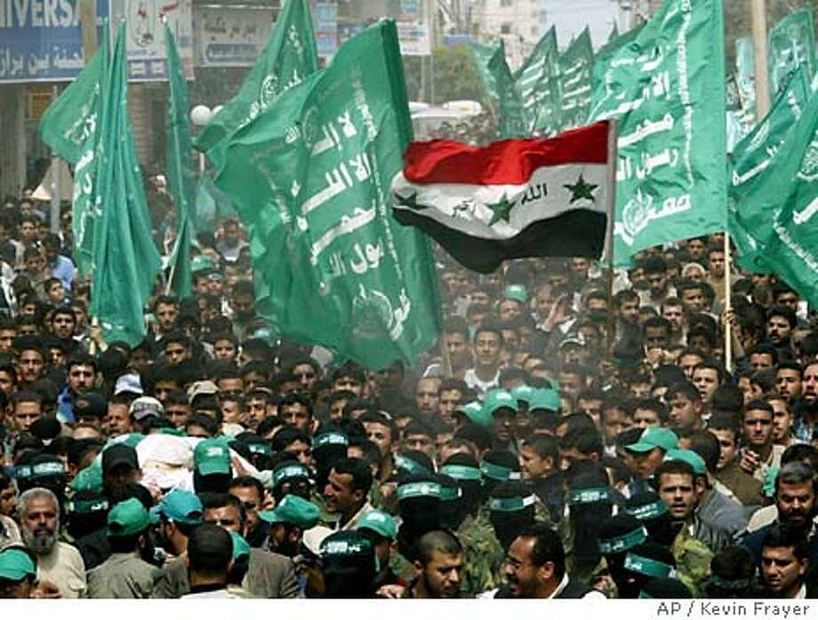 Palestinians carry the body of the late Hamas leader Abdel Aziz Rantisi, bottom left, through the streets during his funeral in Gaza City, early Sunday, April 18, 2004. Rantisi and two bodyguards were killed in an Israeli missle attack on the car they were driving in Saturday in Gaza City. Iraqi flag is seen at center amidst a sea of green Hamas flags. (AP Photo/Kevin Frayer) Photo: KEVIN FRAYER