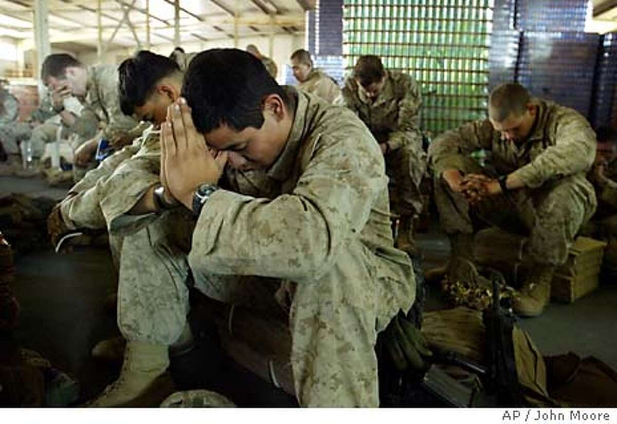 U.S. Marines from the 1st Battalion 5th Marine Regiment pray during a Christian service at their oupost at a soft drink factory in Fallujah, Iraq Sunday, April 18, 2004.(AP Photo/John Moore)