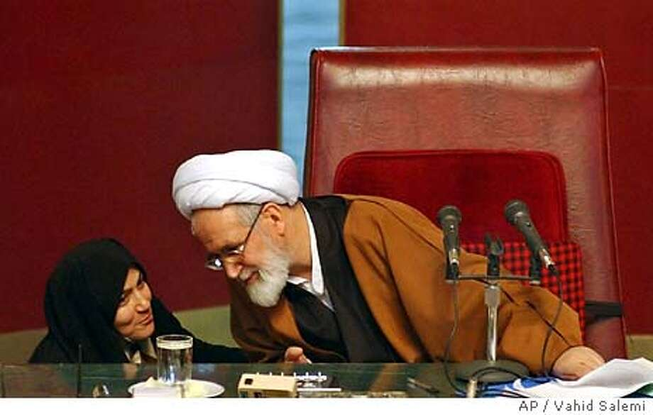 Iranian female lawmaker Akram Mosavvarimanesh, left, talks with speaker Mehdi Karrubi, in an open session of parliament in Tehran, Iran, Tuesday, Feb. 24, 2004. Candidates considered loyal to Iran's Islamic rulers regained control of parliament, denying liberals an important forum in their drive to ease social and political restrictions, according to results Monday from the country's disputed elections.(AP Photo/Vahid Salemi) Photo: VAHID SALEMI