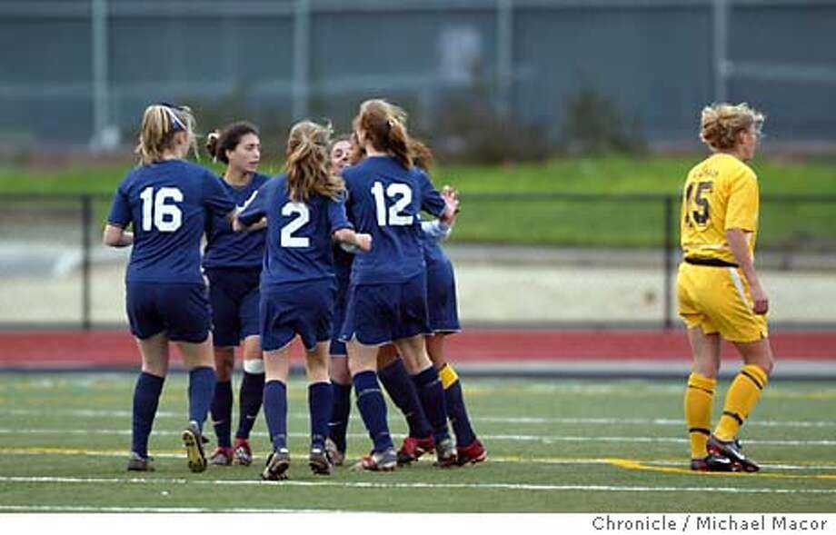 The game first and onl;y goal scored by Notre Dame's 24- Michelle Ancelj in the first half, teammates surround her in celebration as Saint Francis 15- Molly Scott passes by. High School Girls, CCS Central Coast Soccer playoffs, Saint Francis vs. Notre Dame-Belmont at Milpitas High School. event on 2/24/04 in Milpitas Michael Macor / San Francisco Chronicle Photo: Michael Macor