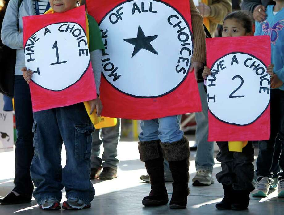"Natalia Ochoa, 5, far right, holds her ""I have a choice 2"" sign with her mother and brother during the Rally for School Choice, at KIPP's East End campus on Saturday, Jan. 28, 2012, in Houston.  During the rally, parents, teachers and community activists called for increased access to strong public schools for all children. Photo: Karen Warren, Houston Chronicle / © 2012  Houston Chronicle"