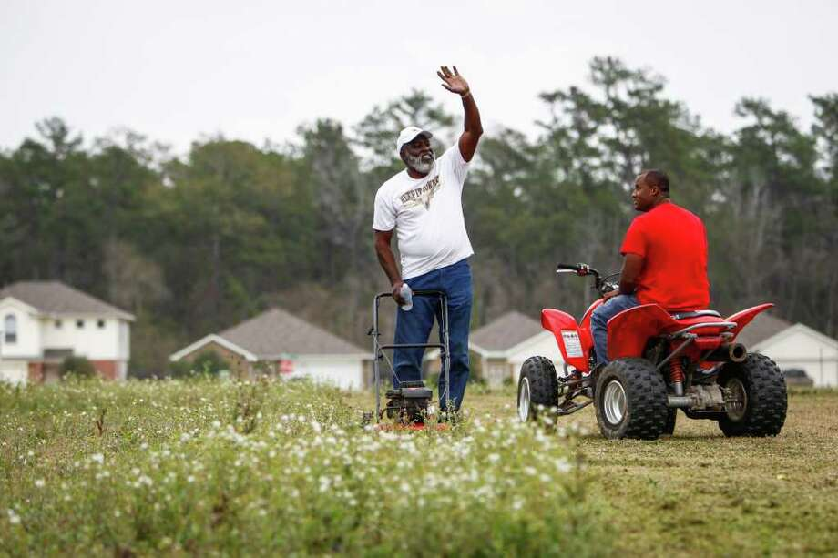 Neighbors Larry Nickelberry, left, and Aundre Johnson tend to a vacant lot near their homes in Leland Woods. Nickelberry is elated that the city has renewed its interest in developing the northeast Houston subdivision. Photo: Michael Paulsen / © 2011 Houston Chronicle